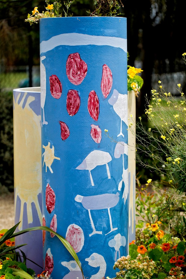 yanni blue painted cylinder with kids paintings and naturtians at base